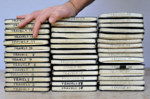 A stack of Moleskine notebooks with a hand resting on top